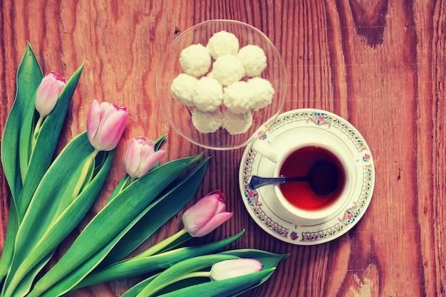 Tło drewniane z tulipanem i herbatą