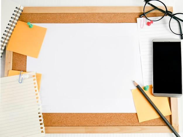 Tło drewnianej deski, papieru, czystego papieru ze sprzętem, takim jak ołówki, okulary, pieniądze, telefony komórkowe i kalendarze,