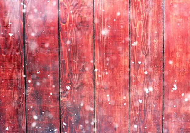 Tło drewnianych desek z efektem bokeh śniegu i brokatu.