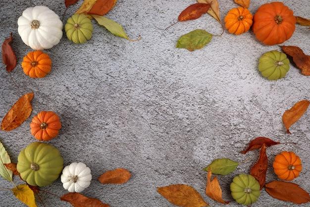 Tło dziękczynienia lub zbiorów z dyni i jesiennych liści