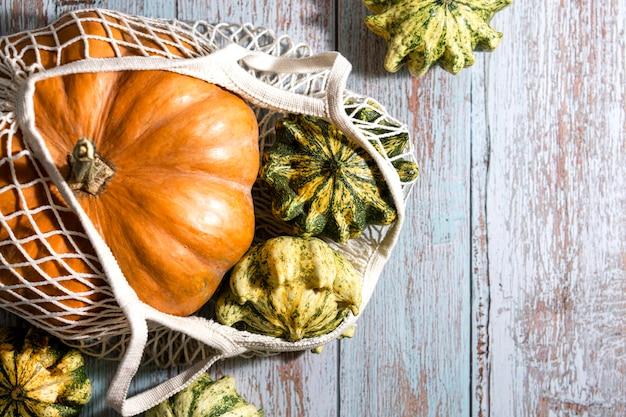 Tło dziękczynienia, skład z jesiennych dyni w ekologicznej torbie na zakupy na podłoże drewniane. wakacje jesienne, zbiory dyni. warzywa sezonowe. zero marnowania. zdrowa żywność naturalna.