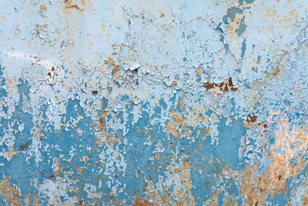 Tło grunge z pękniętą niebieską farbą i rdzą