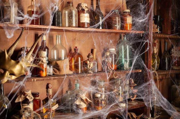 Tło halloween półki z narzędziami alchemicznymi butelka pajęczyny czaszki z zatrutymi świecami obszar roboczy wiedźmin straszny pokój