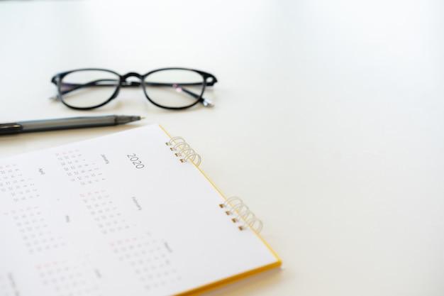 Tło harmonogram kalendarza z piórem i okularami do planowania pracy w rezolucji nowego roku 2020