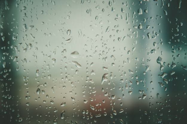 Tło i tapeta przez deszczową kroplę i krople wody na szybę.