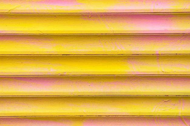 Tło i tekstura metalowych bram w kolorach żółtym i różowym.