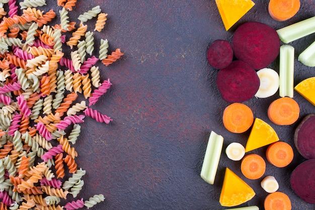 Tło jasny kolorowy suchy makaron z warzyw i jego naturalnych barwników warzywnych seler, burak, marchew, dynia, pasternak. koncepcja zdrowej żywności
