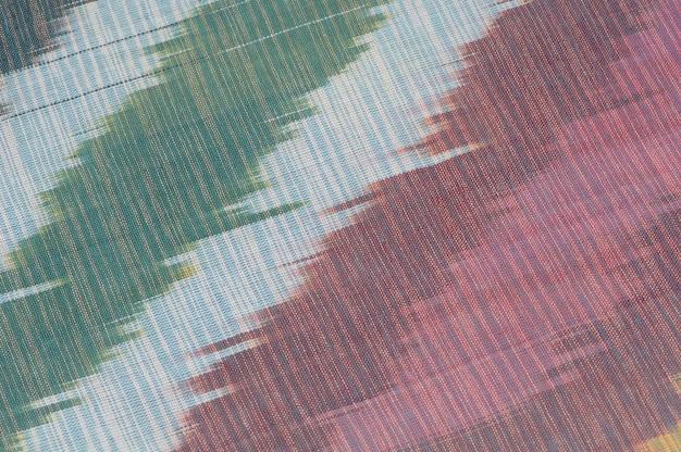 Tło jedwabnej tkaniny z orientalnymi ornamentami. uzbecki jedwab z ornamentem