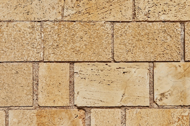 Tło kamiennego muru zamku wykonanego z kamieni o różnych kształtach i rozmiarach i fakturach.