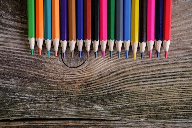 Tło kolorowe kredki na starej drewnianej desce