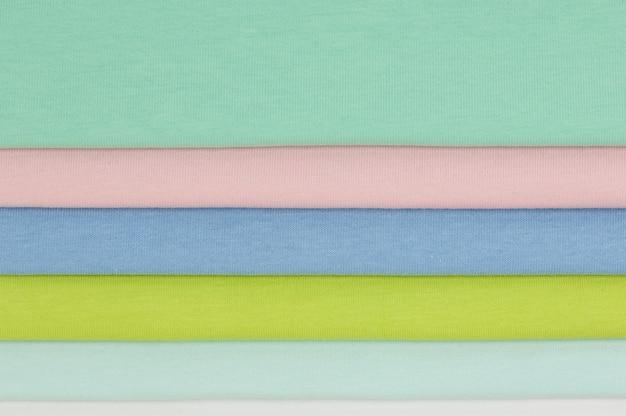 Tło kolorowych tkanin i tekstyliów ułożonych jeden na drugim