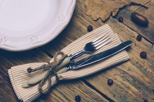 Tło koncepcja obiad na święto dziękczynienia: biały talerz, łyżka i widelec na drewnianym stole rustykalnym z jesiennych liści, czerwonych jagód i żołędzi