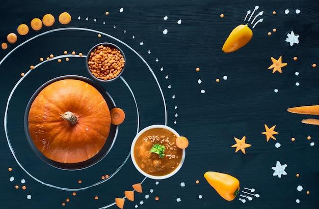Tło koncepcja zdrowej żywności. układ słoneczny dyni kosmicznej z zupą z marchwi, pieprzu i soczewicy.