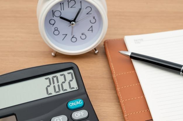 Tło koncepcji biznesowej z kalkulatorem i pamiętnikiem oraz reprezentującym pióro
