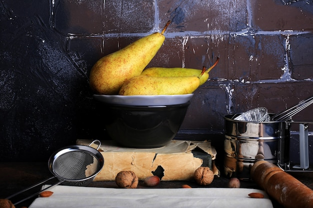 Tło kuchenne pieczenie w stylu retro cegła grunge ściana gruszka migdałowa ciasto filo wałek do ciasta sito