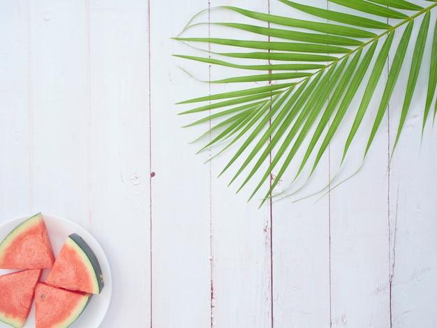 Tło lato. arbuz z liśćmi palmowymi