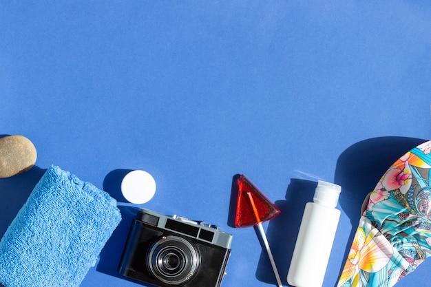 Tło lato z akcesoriami dla podróżników aparat, ręcznik, strój kąpielowy i krem do opalania
