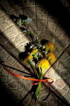 Tło lato z bukietem żółtych kwiatów mniszka lekarskiego na kamiennym bruk