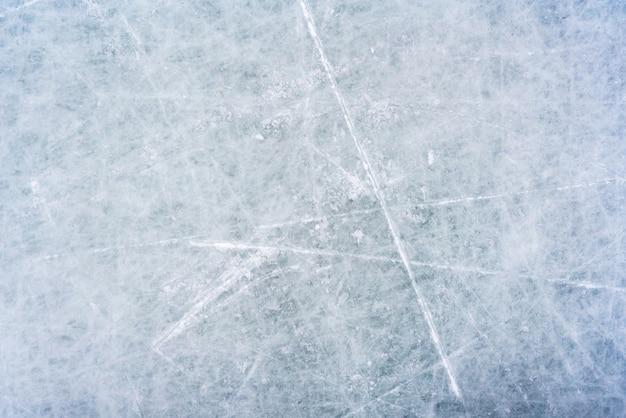 Tło lodu ze śladami na łyżwach i hokeju, niebieska faktura powierzchni lodowiska z zadrapaniami