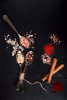 Tło, łyżki z płatkami soli, pieprzem i cynamonem na czarnym kamieniu