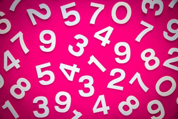 Tło matematyki wykonane z liczb stałych na pokładzie. widok z góry, na różowym tle