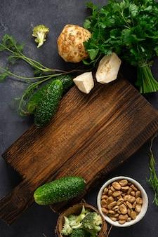 Tło menu żywności. nieociosana drewniana tnąca deska z składnikami dla gotować weganinu jedzenie na ciemnego tła odgórnym widoku