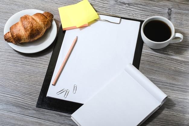Tło miejsca pracy: schowek, kawa, notatnik, pyszny rogalik na drewnianym stole