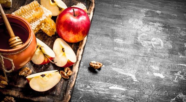 Tło miodu. miód w garnku z plastrami dojrzałych jabłek i orzechów.