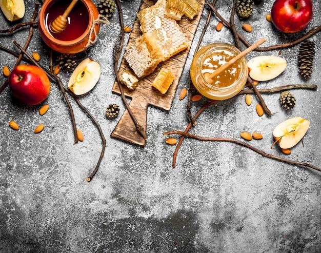 Tło miodu. miód z jabłkami i orzechami na rustykalnym stole.