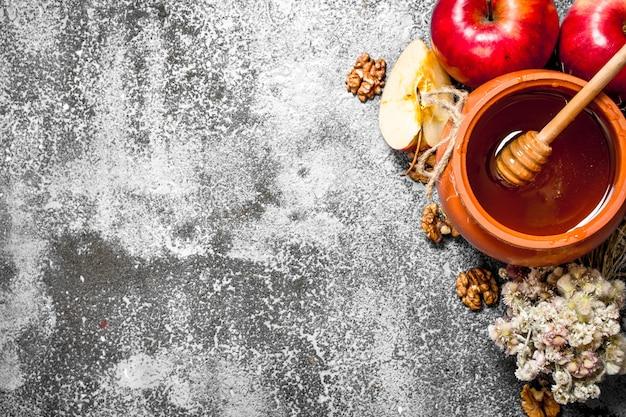 Tło miodu. pachnący miód w garnku z jabłkami i ziołami na rustykalnym stole.