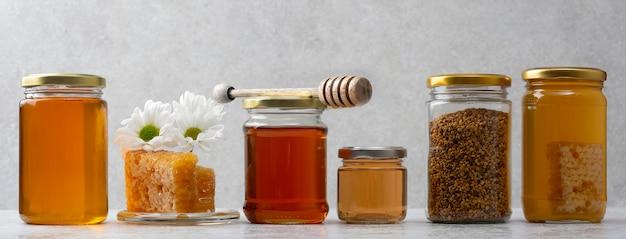 Tło miodu. słodki miód w grzebieniu. różnorodność miodu w szklanych słoikach i plastry miodu na stole.