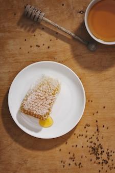 Tło miodu. słodki miód w grzebieniu. świeży miód w szklanym słoju, plastry miodu, łyżka do miodu i pszczoła na jasnym tle. obejrzeć.