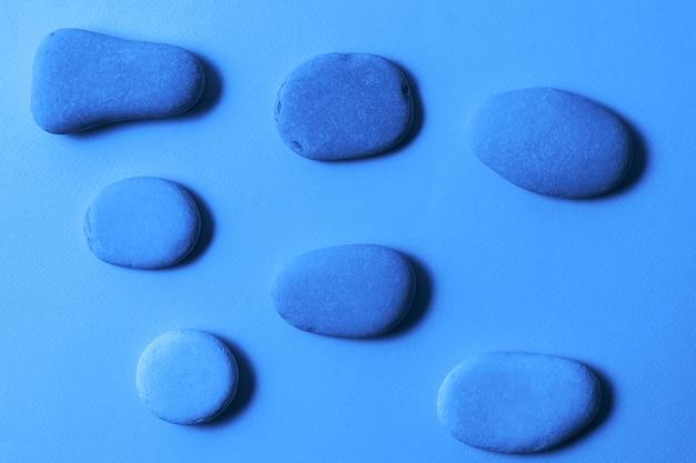 Tło modny klasyczny niebieski kolor z kamieniami plaży morskiej. kolor roku 2020.