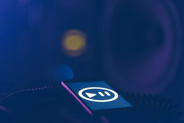 Tło muzyczne z telefonem i ikoną muzyki i kolumną, koncepcja nowoczesnych technologii, słuchanie muzyki.