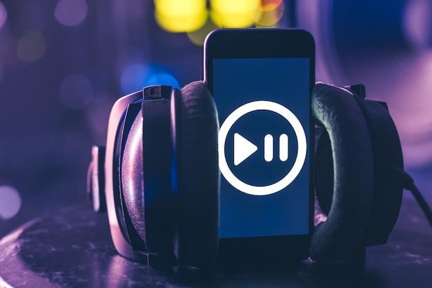 Tło muzyczne z telefonem i ikoną muzyki, koncepcja nowoczesnych technologii, słuchanie muzyki.
