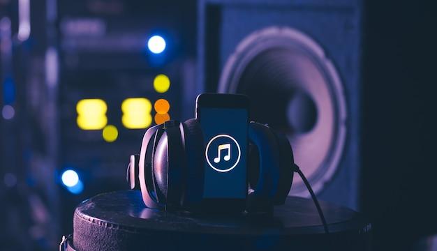 Tło muzyczne z telefonem i słuchawkami na ciemnym tle.