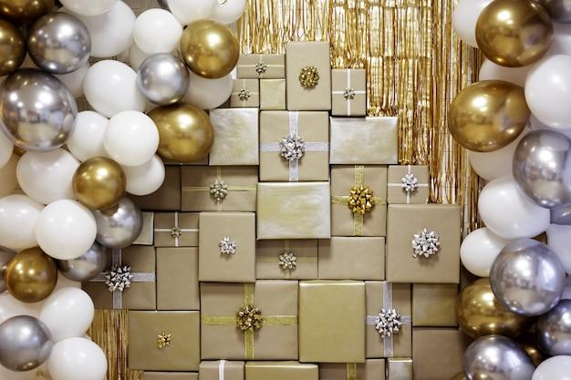 Tło na boże narodzenie, nowy rok lub urodziny - ozdobiona ściana ze złotymi i srebrnymi balonami i zawiniętymi pudełkami prezentowymi