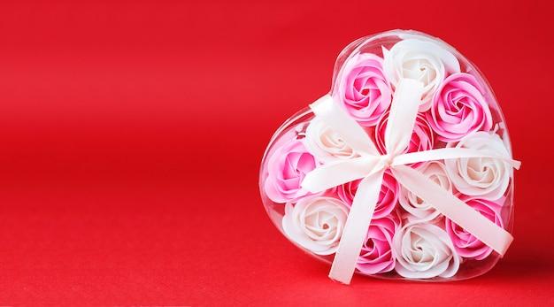 Tło na walentynki. pudełko w kształcie serca z różowymi kwiatami mydła, na białym tle na czerwonym tle