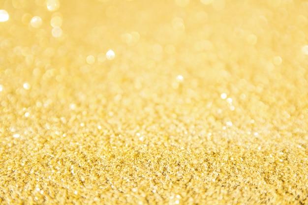 Tło niewyraźne złotym brokatem. złocisty abstrakcjonistyczny bokeh tło.