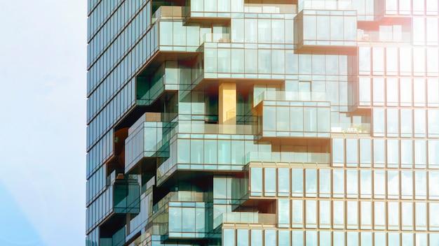Tło nowożytnego budynku architektury ściany błękitny szklany glazurowanie w deseniowym sześcianie i kwadratowym nasunięciu z oświetleniowym światłem słonecznym