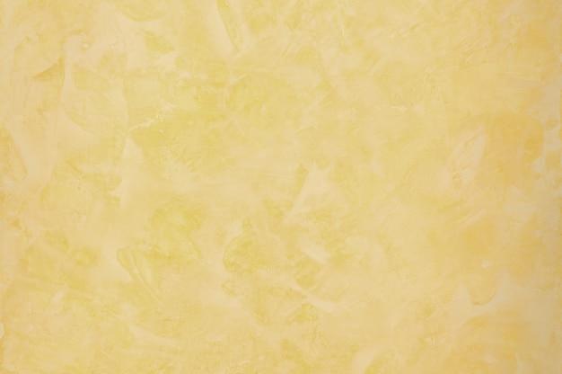 Tło o fakturze tynkowanej z efektem marmuru w kolorze złotym. tło artystyczne ręcznie robione