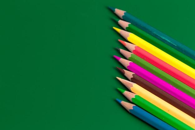 Tło od kolorów ołówków na zielonym papierze