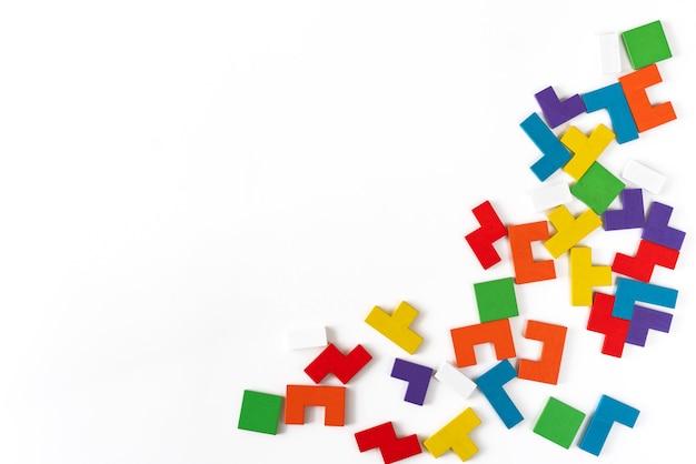 Tło od kolorowych różnych kształtów drewnianych bloków na białym tle. naturalne, ekologiczne zabawki dla dzieci. koncepcja kreatywnego, logicznego myślenia. leżał płasko. skopiuj miejsce