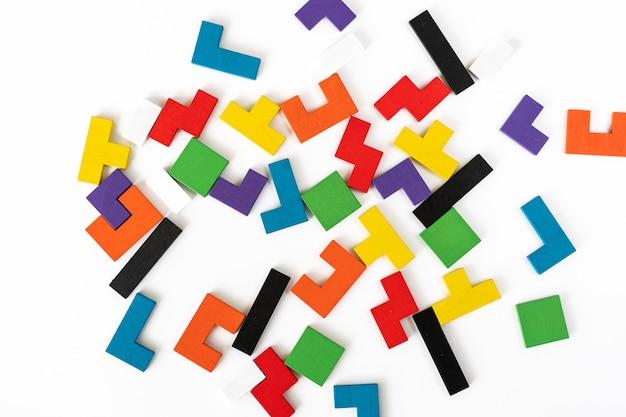Tło od kolorowych różnych kształtów drewnianych bloków na białym tle. naturalne, ekologiczne zabawki dla dzieci. koncepcja kreatywnego, logicznego myślenia. leżał płasko.