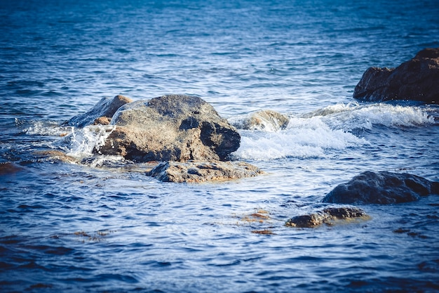 Tło ogromne skały w morzu w pobliżu brzegu, filtr