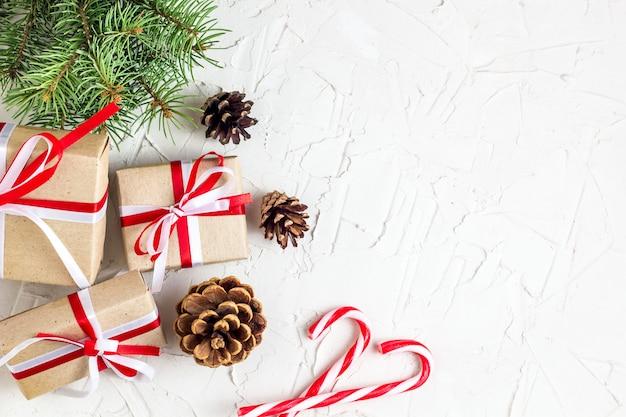 Tło ozdoby świąteczne lub noworoczne z szyszek sosny, gałęzie jodły, pudełka na prezenty i laski cukierki