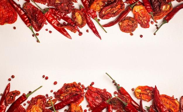 Tło papryki i pomidorów suszone gorące papryczki chili i czerwone suszone pomidory na białym talerzu przyprawy i warzywa jedzenie minimalne płaskie położyć tło koncepcja wysokiej jakości zdjęcie