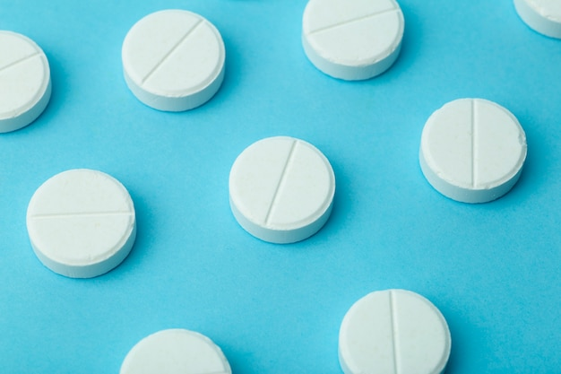 Tło pigułki. pigułki, dragi i koncepcja medyczna. białe tabletki na niebieskim tle