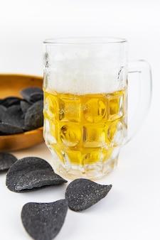 Tło piwa. świeże piwo i chipsy ziemniaczane w drewnianym talerzu. wolne miejsce na tekst.