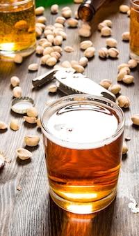 Tło piwa szklanka piwa i pistacji na drewnianym stole